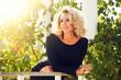 Leinwanddruck Bild - Elegant blonde woman with curly hair in a black dress in the gazebo in the sun.