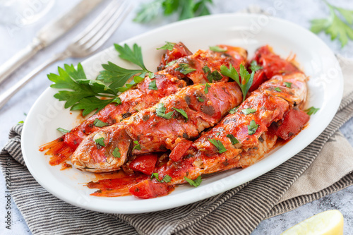 Fotografiet Red mullet or goatfish in tomato sauce with fresh parsley served on a white plate