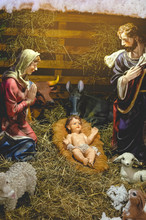Christmas Nativity Scene With The Holy Child, The Blessed Virgin Mary, Saint Joseph, Ox And Donkey In Evening. Selective Focus, Noise Effect