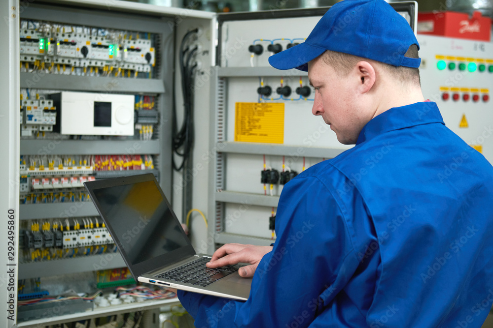 Fototapety, obrazy: Electrician works with tester in switchbox