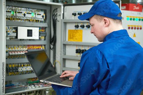 Obraz na płótnie Electrician works with tester in switchbox