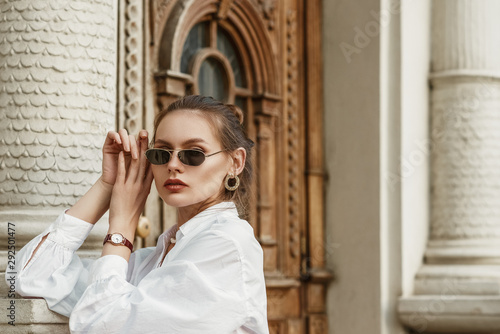 Fotografia Outdoor fashion portrait of elegant, luxury brunette woman wearing black sunglasses, circle earrings, brown wrist watch, trendy white shirt, posing in street of European city