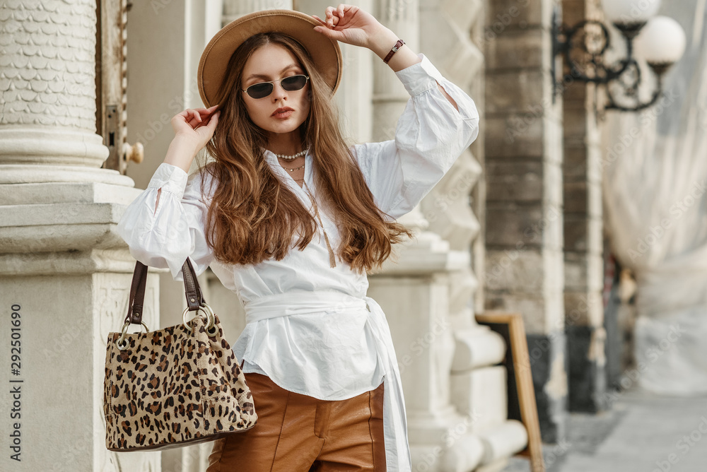 Fototapety, obrazy: Outdoor fashion portrait of elegant, luxury lady wearing beige hat, black sunglasses, trendy white shirt, brown leather trousers, holding animal, leopard print handbag. Copy, empty space for text