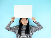 Asian Girl In Winter Costume Holding White Blank Paper On Blue Background.