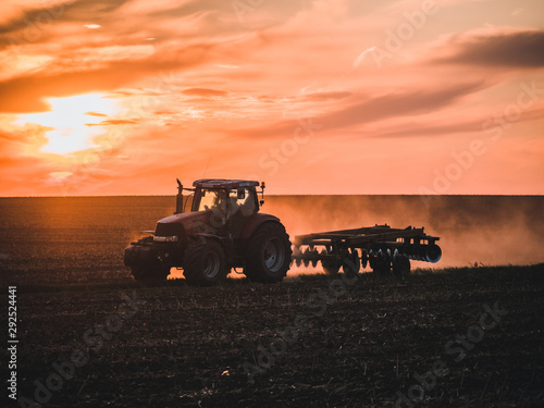 Tractor on filed by sunset. Canvas Print