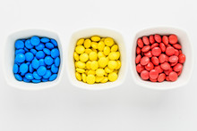 Three Squared Bowls With Small Red, Yellow And Blue Coated Chocolate Candies Similar To M&ms In A Squared Bowl Isolated On White Background, Top View,  Romania Flag Colors