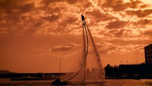 Man Is Practicing Flyboarding In Sunset Time On Sea, Moving Over Water Surface On Flows