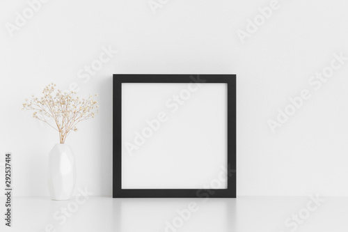 Fototapety, obrazy: Black square frame mockup with a gypsophila in a vase on a white table.