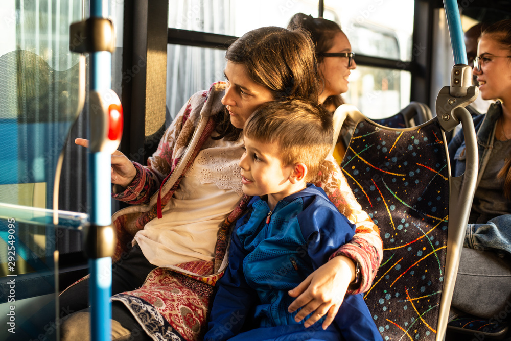 Fototapety, obrazy: Close up of mother holding her son in public transportation