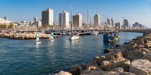 Miniature And Other Sailboats In The Marina In Tel Aviv In Israel Showing Yachts And Resort Hotels In The Background And Breakwater Stones In The Foreground