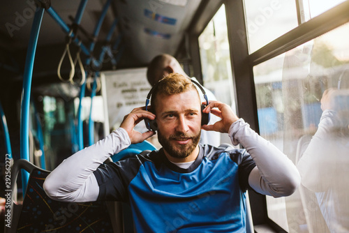 Young man in bus listening to music - 292562272
