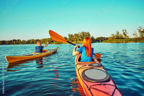 Poster Turquoise People kayak during sunset in the background. Have fun in your free time.