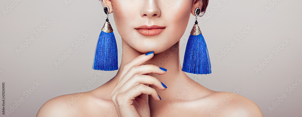 Fototapeta Beautiful woman with large earrings tassels jewelry blue color. Perfect makeup and nails manicure