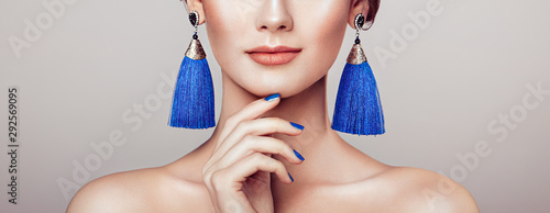 Photo Beautiful woman with large earrings tassels jewelry blue color