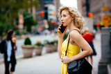 Fototapeta Nowy Jork - Profile portrait of a young woman talking on the phone in the city