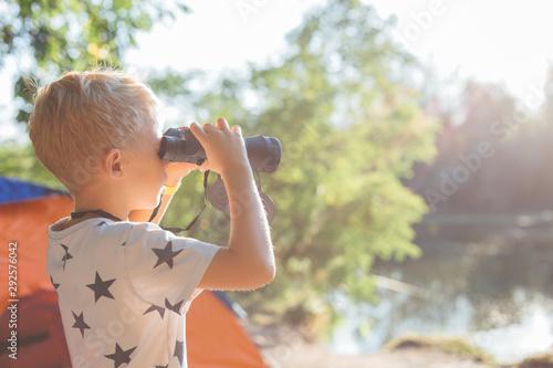Canvastavla  Happy boy looking through binoculars at lake