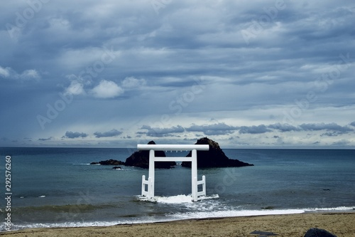 Wide shot of Itoshima beach in Fukuoka, Japan during twilight with white torii gate in the center