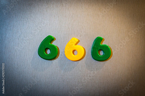 Photo The number 666 made of magnetic objects on silver background.