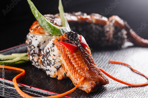 Fototapeta Sushi dragon with eel, cucumber and avocado on a black background. Japanese food, tasty of meal for lunch obraz