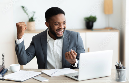 Happy black businessman rejoicing success at workplace in office