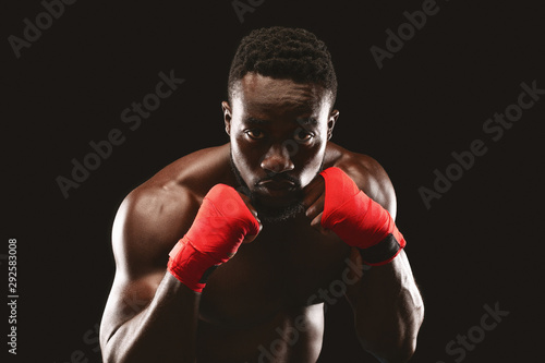 Fotografía Professional fighter in boxing stance posing over black studio background