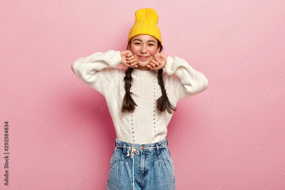 Fototapety, obrazy: Pretty mixed race female dressed in fashionable yellow hat, white sweater and jeans, has enthusiastic and charming look in camera, glad expression, isolated over pink background, has two combed plaits