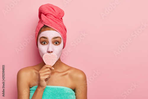 Photo sur Toile Ecole de Danse Horizontal shot of surprised lady covers mouth with heart shaped sponge, removes makeup, applies clay mask on face for looking young, wears wrapped towel on head, poses over pink wall, copy space