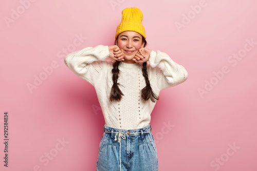 Pinturas sobre lienzo  Pretty mixed race female dressed in fashionable yellow hat, white sweater and je