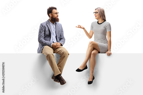 Young woman having a conversation with a bearded man while sitting on a panel Wallpaper Mural
