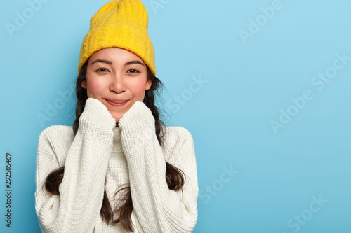 Obraz Portrait of delighted adorable Asian woman keeps hands under chin, dressed in oversized white sweater and yellow hat, enjoys comfort and calm domestic atmosphere, stays at home during cold weather - fototapety do salonu