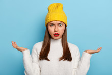 Portrait Of Beautiful Young Caucasian Girl Being Questioned, Spreads Palms Sideways, Feels Unawareness And Doubt, Wears Red Lipstick, Wears Yellow Stylish Hat, White Jumper, Isolated On Blue