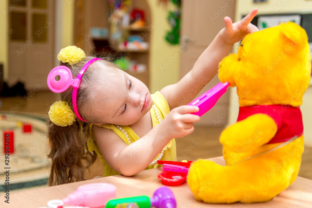 Fototapety, obrazy: Girl with down syndrom playing doctor with toy bear, rehabilitation center