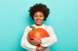 canvas print picture - Autumn harvesting, food and Halloween holiday concept. Cheerful curly African American woman embraces ripe pumpkin, smiles pleasantly, dressed in white sweater. Girl with thanksgiving symbol.