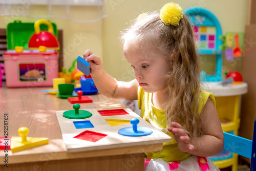 Photo Girl with down syndrom developing motor skills in rehab center for special child