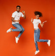 canvas print picture - Carefree african american man and woman jumping in air