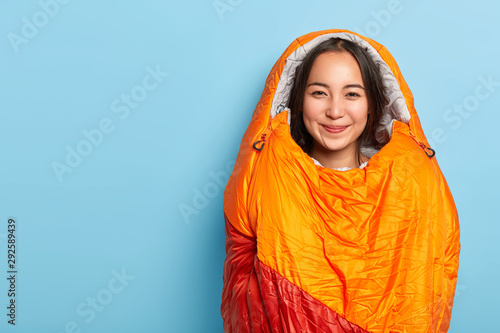 Pleased young Asain brunette woman wrapped in warm orange sleeping bag, spends f Wallpaper Mural