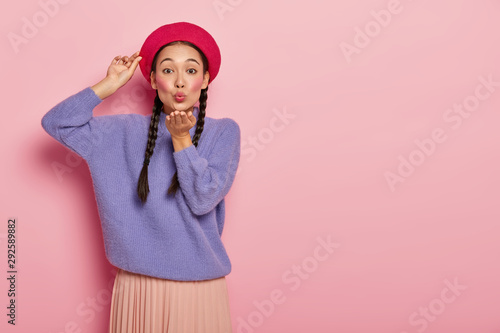 Obraz Adult korean woman keeps lips rounded, sends air kiss, blows mwah, keeps one hand on red beret, wears makeup, oversized purple sweater, expresses romantic passionate feelings, models indoor. - fototapety do salonu