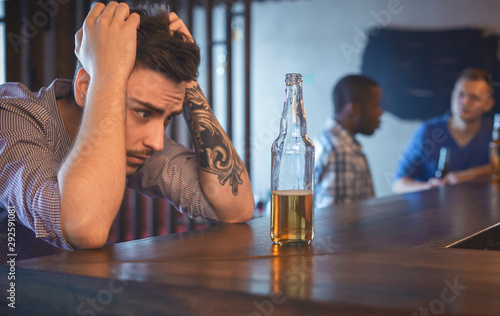 Fotomural Troubled young man sitting alone at bar
