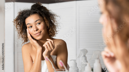 Obraz na plátně  Young Lady Applying Cream Under Eyes Looking In Bathroom Mirror