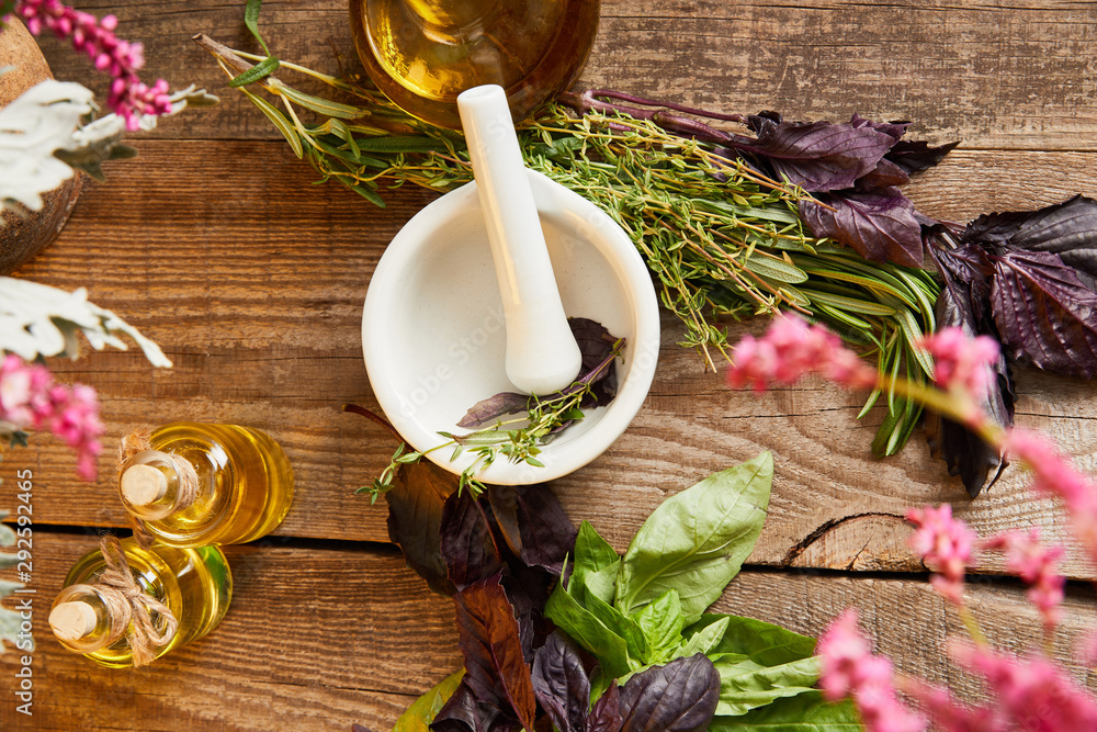 Fototapety, obrazy: top view of mortar with pestle near bottle and fresh leaves and flowers on wooden surface