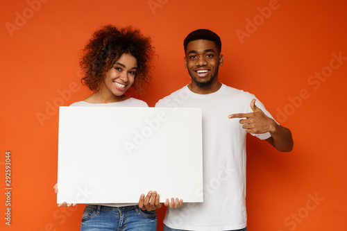 Leinwand Poster Positive black man and woman pointing at white empty board
