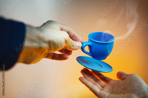 Photo Stands Tea Floating blue cup of espresso with hands. First-person view. Mock up of soaring in the air cup of hot coffee. Levitate concept