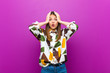 canvas print picture - young pretty woman looking unpleasantly shocked, scared or worried, mouth wide open and covering both ears with hands against purple background