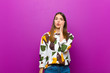 canvas print picture - young pretty woman feeling shocked and astonished holding face to hand in disbelief with mouth wide open against purple background
