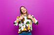 canvas print picture - young pretty woman smiling broadly looking happy, positive, confident and successful, with both thumbs up against purple background