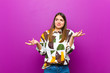 canvas print picture - young pretty woman shrugging with a dumb, crazy, confused, puzzled expression, feeling annoyed and clueless against purple background