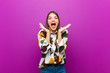 canvas print picture - young pretty woman feeling shocked and excited, laughing, amazed and happy because of an unexpected surprise against purple background