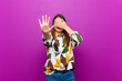 canvas print picture - young pretty woman covering face with hand and putting other hand up front to stop camera, refusing photos or pictures against purple background