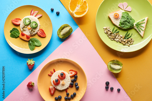 top view of plates with fancy animals made of food for childrens breakfast on blue, yellow and pink background
