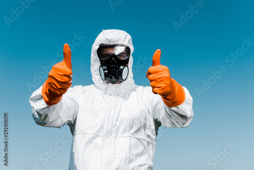 Cuadros en Lienzo  exterminator in protective mask and uniform standing and showing thumbs up